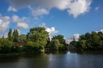 Bruges lake and park under a sunny sky.