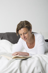 Smiling Woman reading a book in bed