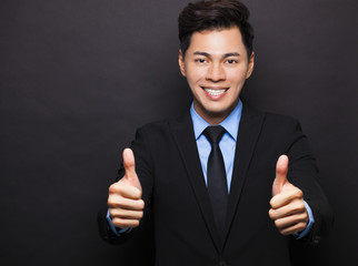 Smiling asian businessman with thumbs up