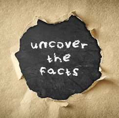 top view of blackboard with the phrase uncover the facts