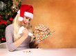 Girl making gingerbread house. Young woman with Santa Hat