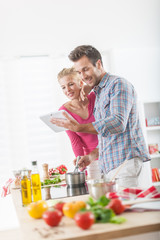 Handsome couple using a digital tablet to cook at home