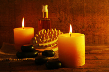 Spa stones, oil and candles on wooden background