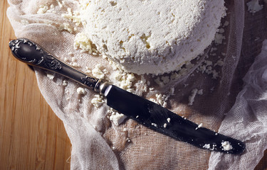 Cottage cheese and metal knife on gauze on cutting board