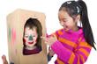 Kinder spielen mit einem Pappkarton