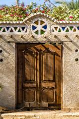 Ägyptische Eingangstür aus Holz in verzierter Mauer