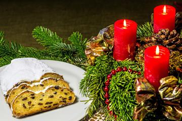 Stollen mit Adventskranz und brennenden Kerzen