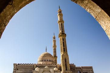 Blick durch Bogen auf Minarett und  Moschee im Sinai