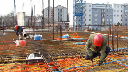Construction workers installing reinforcement steel bars