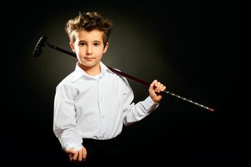 Little boy with golf club low key studio portrait