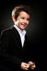Little boy businessman portrait in low key counting money