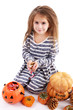 Little girl Witch with pumpkins and candy isolated on white