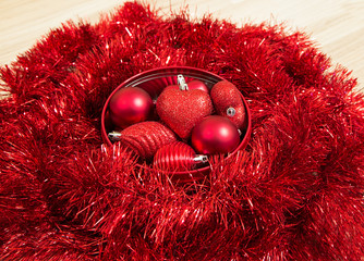 red christmas baubles on sparkling red wreath isolated on wooden