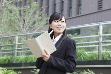 ノートを見て考えるビジネスウーマン