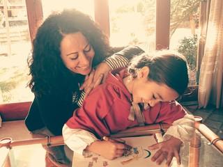 Madre viendo dibujar a su hija