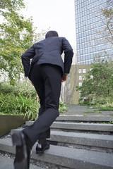 階段を駆け上がるビジネスマン