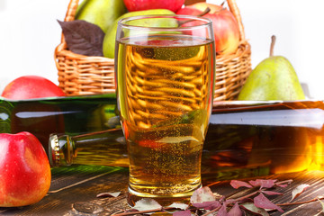 Glass and bottles of cider, fruits basket with apples and pears