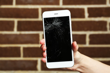Broken iPhone in hand on brick background