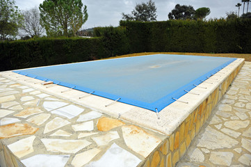 Swimming pool protected with a blue tarp, winter