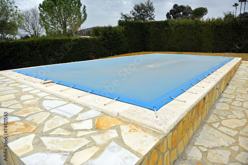 Swimming pool protected with a blue tarp, winter - 74421563