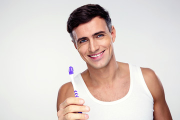Happy man holding toothbrush on gray background