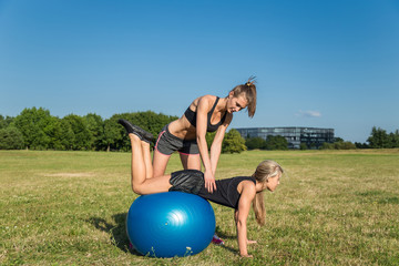 Pretty young woman couple training with balance ball in the park