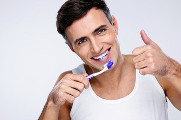 Young man brushing his teeth over gray background