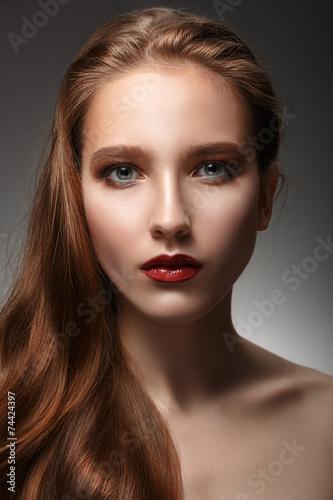 Póster Hermosa mujer con la piel perfecta y el pelo largo en un backgr gris