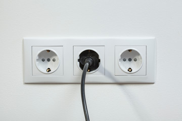 Black power plug plugged in a electric socket