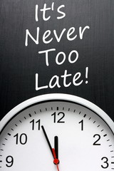 It's Never Too Late written on a blackboard above a clock face
