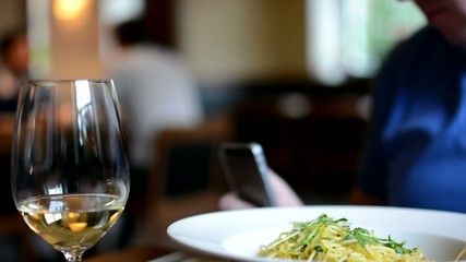 man in restaurant works on smartphone - wine and spaghetti