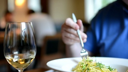 restaurant - man eats spaghetti - wine - people in background