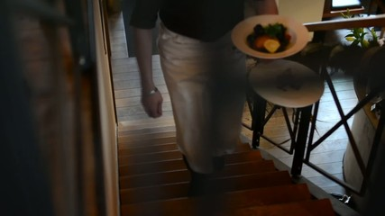 waiter carries food in restaurant - staircase