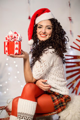 Portrait of lovely woman in xmas cap with present