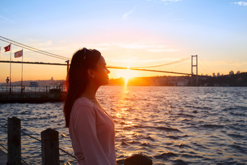 Young girl on background of Bosphorus bridge and sunset