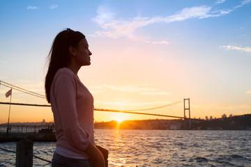 Young girl on background of Bosphorus bridge and sunset