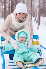 Happy family mother and baby in park in winter