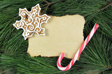 blank christmas card on fir tree with gingerbread and candy