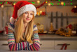 Portrait of happy young woman in christmas decorated kitchen
