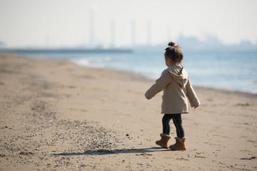 冬の砂浜を歩く少女