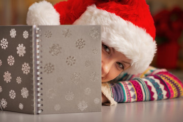 Teenager girl in santa hat looking out from notepad
