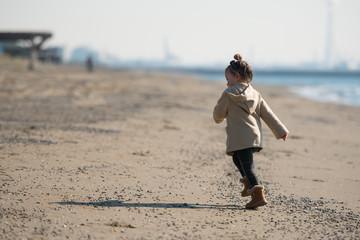 冬の砂浜を走る少女