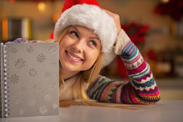 Portrait of thoughtful teenager girl in santa hat with notepad