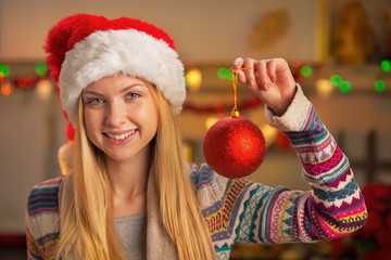 Portrait of smiling  girl in santa hat showing christmas ball