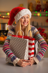 Portrait of happy girl in santa hat hugging shopping bags