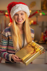 Portrait of smiling girl in santa hat with christmas present box