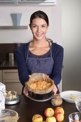 Junge Frau zeigt stolz ihren Apfelkuchen