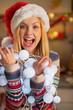 Portrait of happy teenager girl in santa hat holding garland