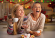 Portrait of laughing girlfriends having christmas snacks