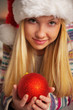 Portrait of teenager girl in santa hat holding christmas ball